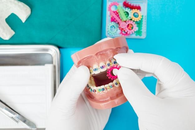 Zahnarztwerkzeuge und kieferorthopädisches modell auf blau Premium Fotos
