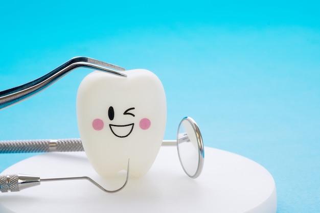 Zahnmedizinische werkzeuge und lächelnzähne modellieren auf blauem hintergrund. Premium Fotos
