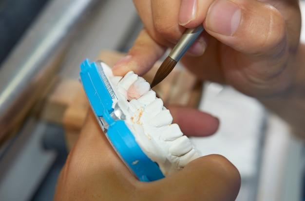 Zahntechniker, der eine bürste mit keramischen zahnimplantaten in seinem labor verwendet Premium Fotos