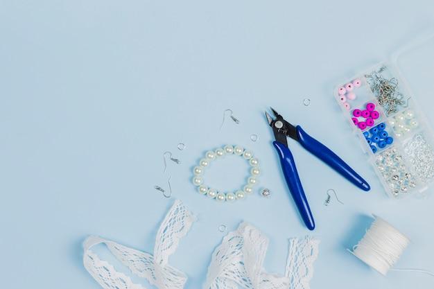 Zange; haken; perlen; spitzenband; fadenspule und kunststoff-perlen-box auf blauem hintergrund Kostenlose Fotos