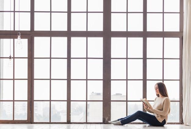 Zangenfrau, die auf fußboden nahe dem fensterlesebuch sitzt Premium Fotos