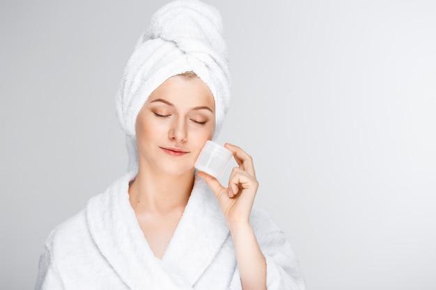 Zarte blonde frau mit badetuch auf haar, das creme zeigt Kostenlose Fotos