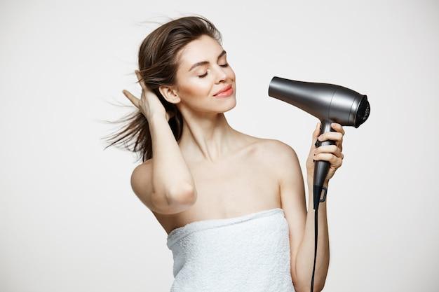 Zarte brünette schöne frau im handtuchtrocknenden haar, das über weißem backgrund lächelt. geschlossene augen. beauty spa und kosmetologie. Kostenlose Fotos