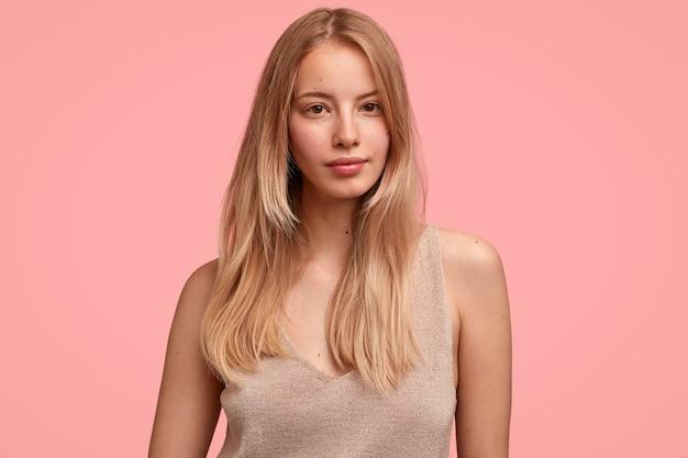 Zarte frau fühlt sich sanft und schön, trägt lässiges beige t-shirt, hat glattes helles haar, isoliert über rosa wand, sieht ernst aus, zeigt natürliche schönheit, hat kein make-up Kostenlose Fotos