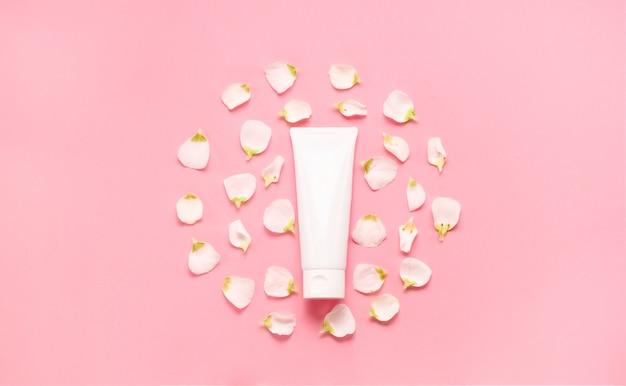 Zarte hautpflege kosmetische weibliche flatlay. draufsicht kreative zusammensetzung von gesichtscreme, flaschen und gläsern mit kosmetik- und blumenblättern auf abstraktem hintergrund Premium Fotos