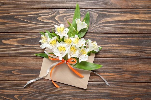 Zarte kleine orchideen der weißen blumen in einem listigen postumschlag auf einem hölzernen hintergrund Premium Fotos