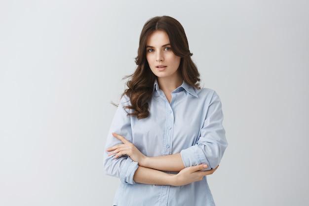 Zarte schöne junge frau mit dunklem welligem haar im blauen hemd, das ernstes aussehen hat und für foto im artikel über junge familien aufwirft. Kostenlose Fotos