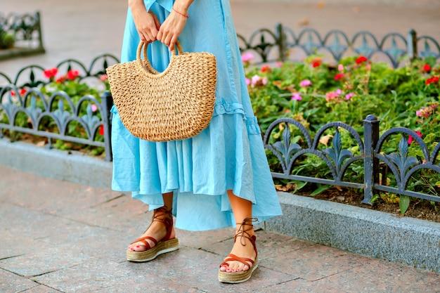 Zarte stilvolle frau, die blaues maxikleid, strohsack und gladiatorensandalen aufwirft und trägt Kostenlose Fotos