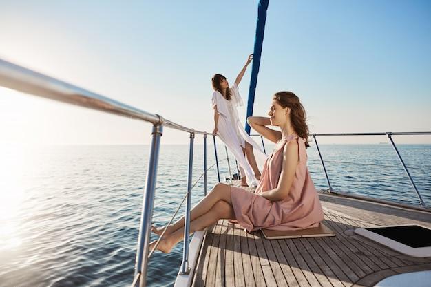 Zarte und attraktive erwachsene frau, die zeit auf dem boot verbringt. frau steht auf trug der yacht mit verträumtem blick, während ihre freundin an der seite sitzt, beide fühlen sich wie im paradies Kostenlose Fotos