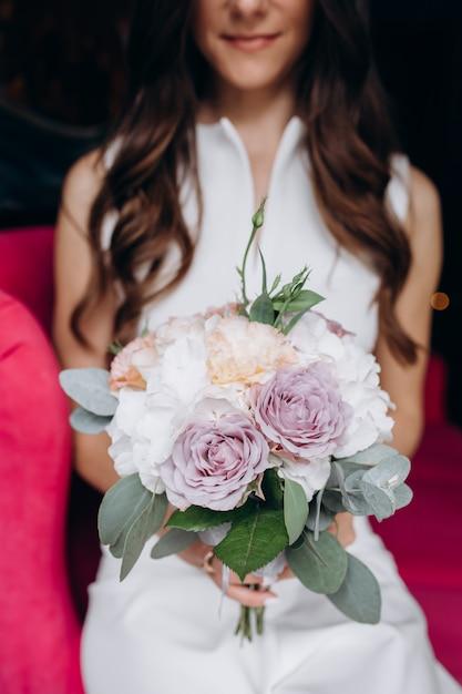 Zarte und reizende braut sitzt mit reichem hochzeitsblumenstrauß auf einer rosa couch im café Kostenlose Fotos