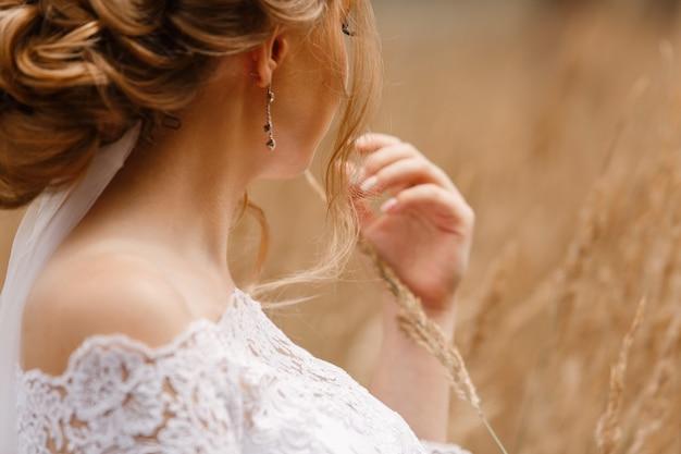 Zartes porträt der braut im weißen kleid draußen auf weizenfeld. hochzeitstag. stilvolle frau mit einem schönen ausschnitt und bloßen schultern mit seitenansicht der frisur. mädchen mit weizenähren in der hand Premium Fotos