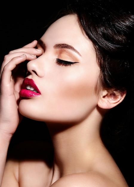 Zaubernahaufnahmeporträt des kaukasischen modells der jungen frau des schönen sexy brunette mit hellem make-up, mit den roten lippen, mit perfekter sauberer haut Kostenlose Fotos