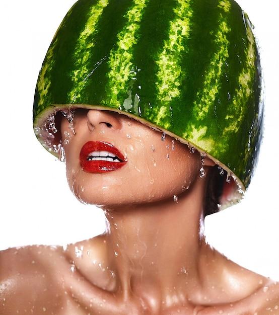 Zaubernahaufnahmeporträt des schönen sexy modells der jungen frau mit wassermelone auf kopf mit wassertropfen Kostenlose Fotos