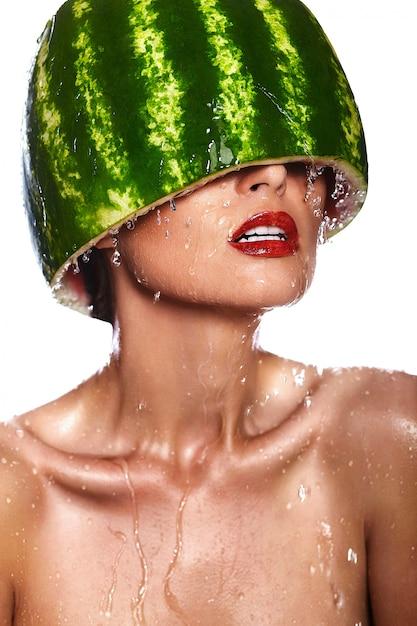 Zaubernahaufnahmeporträt des schönen sexy modells der jungen frau mit wassermelone auf kopf Kostenlose Fotos