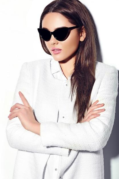 Zaubernahaufnahmeporträt des schönen sexy stilvollen modells der jungen frau des brunettegeschäfts im weißen manteljackenhippie-stoff in der sonnenbrille Kostenlose Fotos