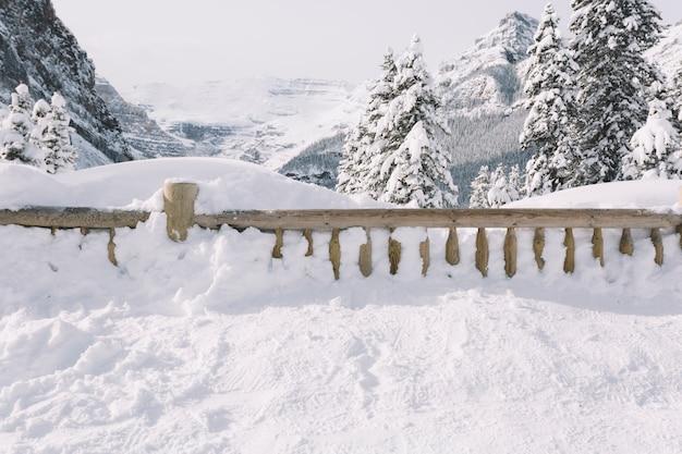 Zaun bedeckt mit schnee in den bergen Kostenlose Fotos