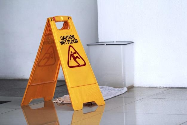 Zeichen, das warnung des nassen bodens der achtung zeigt. bodenbelagzeichen. Premium Fotos
