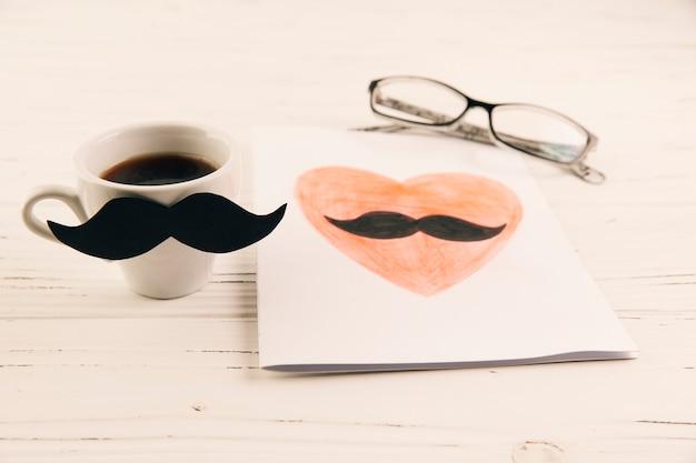 Zeichnen auf papier nahe cup des getränks und der brillen Kostenlose Fotos