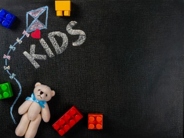 Zeichnen auf sandpapier. die kinder, die auf tafel und teddybären mit geschrieben werden, bauen stücke zusammen. hintergrund textfreiraum. Premium Fotos