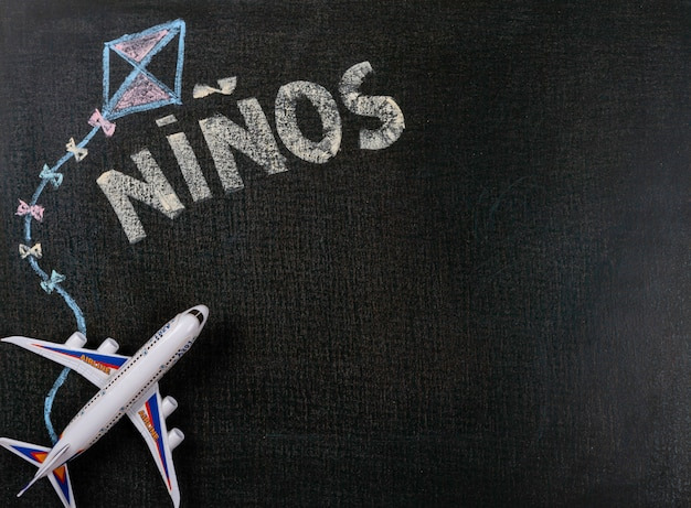 Zeichnen auf tafel. niños (spanisch) geschrieben auf tafel- und flugzeugspielzeug. hintergrund textfreiraum. Premium Fotos