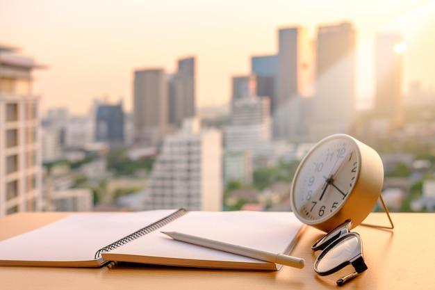 Zeichnen sie auf notizbuch- und alam-uhrbrillen mit goldenem hellem unschärfen-sonnenunterganghintergrund an. Premium Fotos