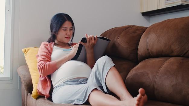 Zeichnungsbaby der schwangeren frau des jungen asiaten im bauch im notizbuch. die mutter, die glücklich sich fühlt, positiv und ruhig lächelnd, während mach s gut das kind, das zu hause auf sofa im wohnzimmer liegt. Kostenlose Fotos