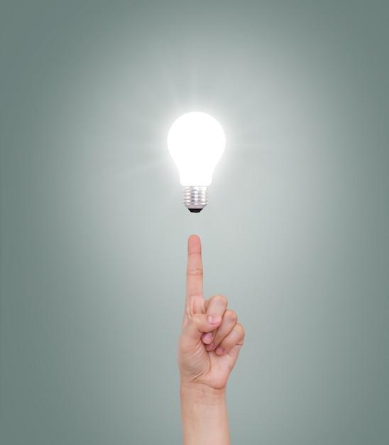 Zeigefinger auf einer beleuchteten glühbirne zeigen Kostenlose Fotos