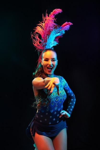 Zeigen. schöne junge frau im karneval, stilvolles maskeradenkostüm mit federn auf schwarzer wand im neonlicht. copyspace für anzeige. feiertagsfeier, tanz, mode. festliche zeit, party. Kostenlose Fotos