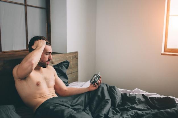 Zeit aufzuwachen. müder mann im bett nicht glücklich. reifer kerl, der wecker bei der prüfung der zeit auf arbeit hält Premium Fotos