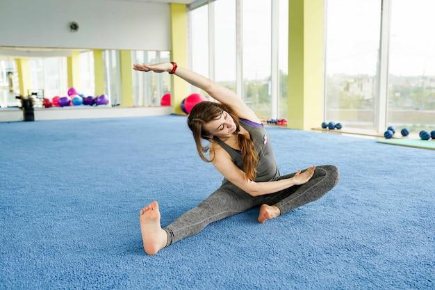 Zeit für yoga. attraktive junge frau, die auf dem boden in der turnhalle trainiert und sitzt Premium Fotos