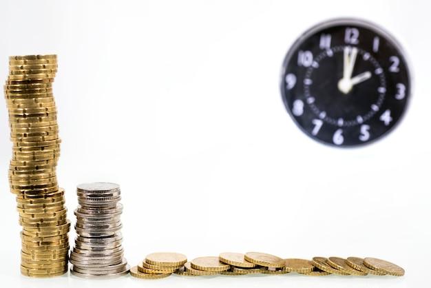 Zeit ist geld konzept: wecker und mit münzen Premium Fotos