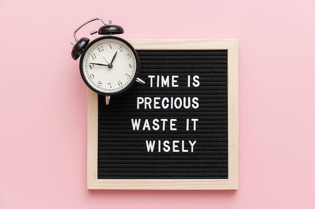 Zeit ist kostbare verschwendung es klug, motivzitat auf briefpapier und schwarzer wecker auf rosa Premium Fotos