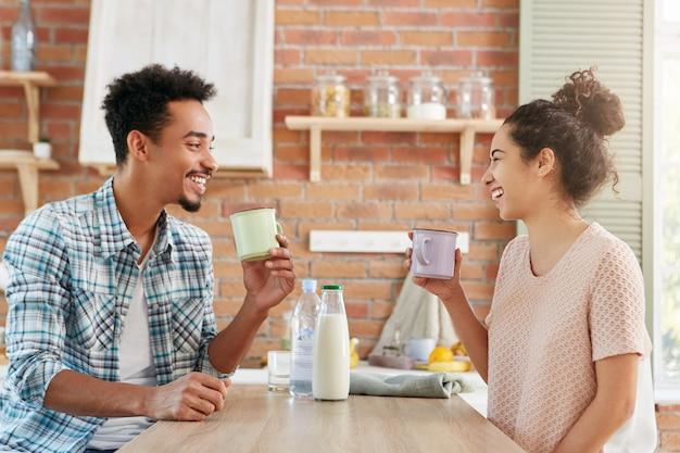 Zeit zu hause zusammen verbringen. fröhlicher bärtiger mann und seine frau trinken morgens tee oder milch, haben gute laune, Kostenlose Fotos
