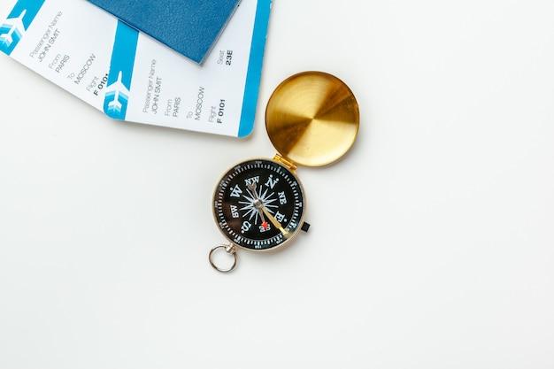 Zeit zu reisen. ideentourismus mit flugtickets und kompass auf weiß Premium Fotos