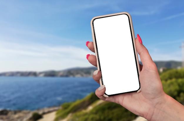 Zeit zu reisen. smartphone in der hand, vor dem hintergrund des meeres und der stadt unter einem sonnigen himmel. Premium Fotos