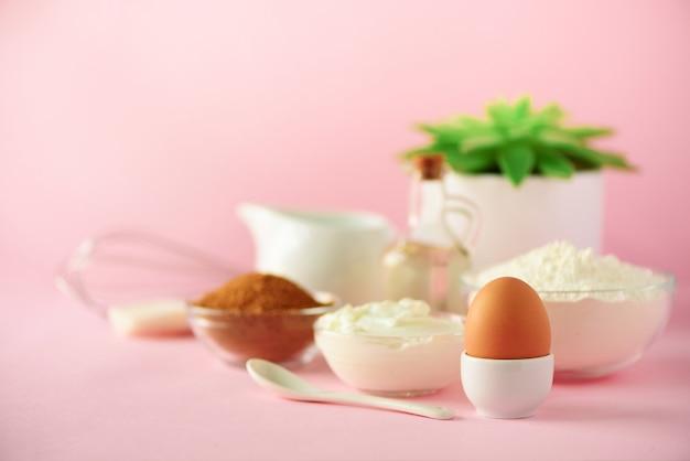 Zeit zum backen. backzutaten - butter, zucker, mehl, eier, öl, löffel, pinsel, schneebesen, milch über rosa hintergrund. bäckereilebensmittelrahmen, konzept kochend. kopieren sie platz Premium Fotos