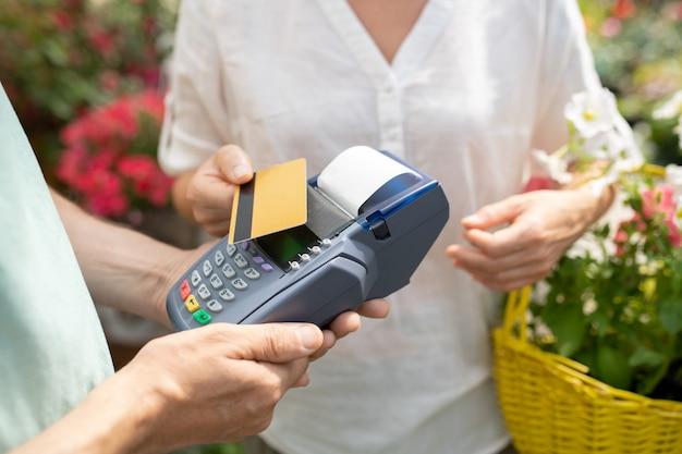 Zeitgenössische käuferin mit kreditkarte, um einige frische topfblumen im zeitgenössischen gartencenter zu bezahlen Premium Fotos