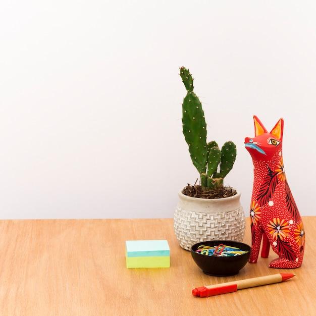 Zeitgenössischer arbeitsplatz mit kaktus im topf und in der statue Kostenlose Fotos