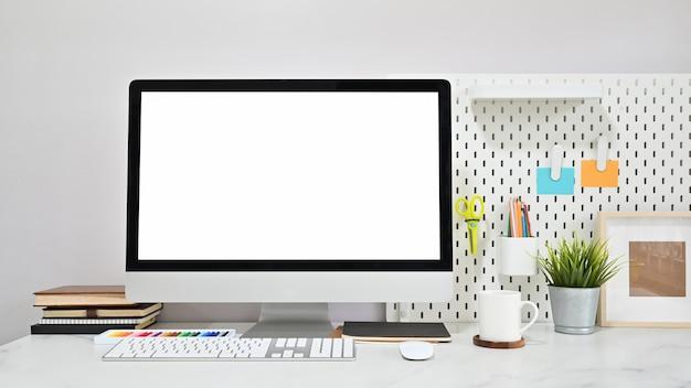 Zeitgenössischer arbeitsplatz mit leerem bildschirmcomputer und büroartikel auf marmortabelle. Premium Fotos