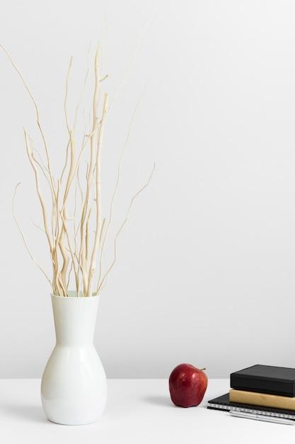 Zeitgenössischer arbeitsplatz mit vase und apfel auf schreibtisch Kostenlose Fotos