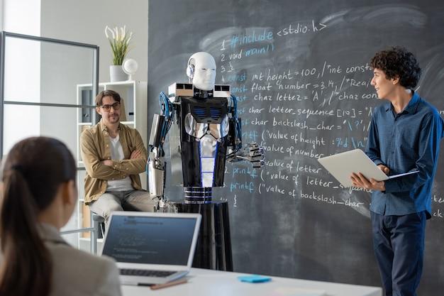 Zeitgenössischer junger student mit laptop, der durch tafel im klassenzimmer steht und präsentation des computerroboters macht Premium Fotos