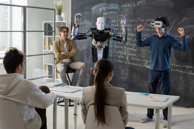 Zeitgenössischer student mit vr-headset, der während der präsentation die fähigkeiten eines automatisierungsroboters vor seinen klassenkameraden demonstriert Premium Fotos