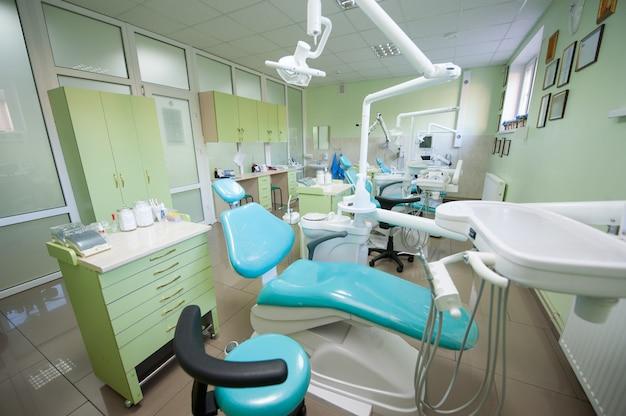 Zeitgenössisches leeres zahnmedizinisches büro mit drei zahnmedizinischen stühlen und ausrüstung Premium Fotos
