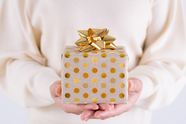 Zeitgeschenkkonzept - geschenkbox mit mädchen des goldbogens in der hand. weihnachts- oder verpackentagskonzept. geburtstag-konzept. Premium Fotos