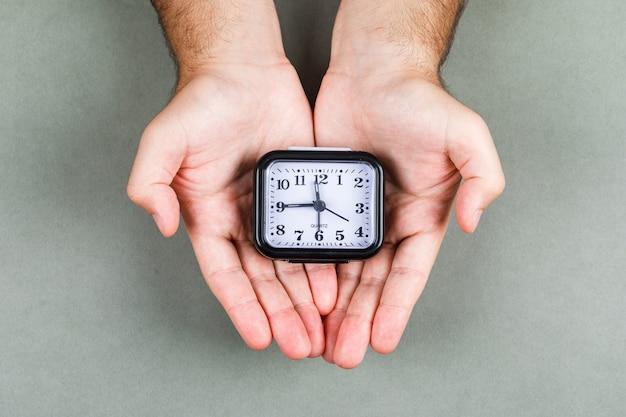 Zeitmanagement und uhr-ticking-konzept mit uhr auf grauer hintergrund-draufsicht. zeiger halten eine uhr. horizontales bild Kostenlose Fotos