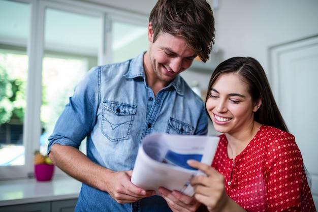 Zeitung des glücklichen paars lesezu hause Premium Fotos