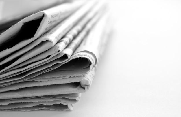 Zeitung mit nachrichtennahaufnahme auf weißem hintergrund Premium Fotos