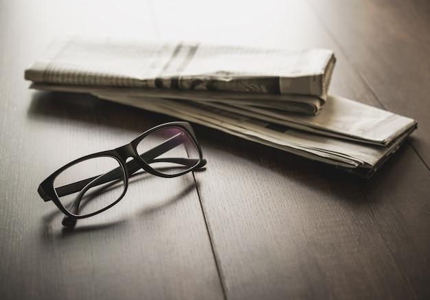 Zeitung und lesebrille auf geschäftsschreibtischgeschäftszeitungshintergrund Premium Fotos