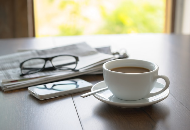 Zeitungslesebrillekaffeetasse und -handy auf geschäftsschreibtischgeschäfts-zeitungshintergrund. Premium Fotos