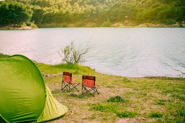 Zelt und campingstühle am see Kostenlose Fotos